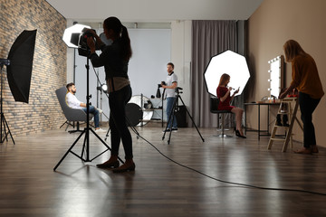 Photo studio with professional equipment and team of workers