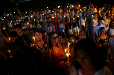 Relative and friends of victims of a collapsed tailings dam owned by Brazilian mining company Vale SA, carry candles as they pay respects during a vigil in Brumadinho