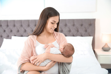 Young woman with her newborn baby in bedroom