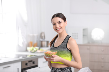 Young woman in fitness clothes holding bowl of cereal breakfast with fruits at home