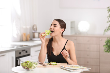 Young woman in fitness clothes eating lettuce while preparing healthy breakfast at home