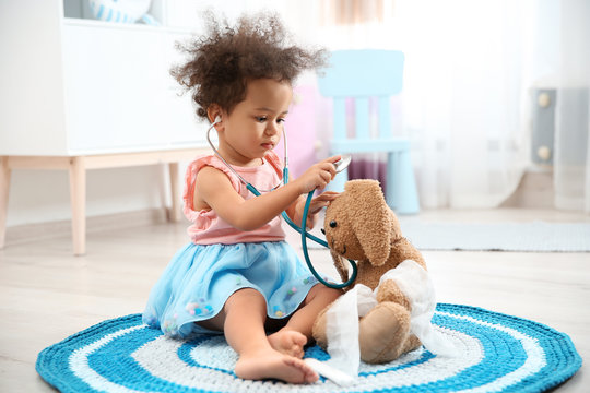 Cute African American child imagining herself as doctor while playing with stethoscope and toy bunny at home