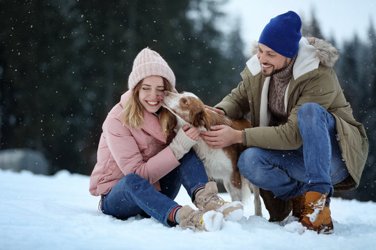 Cute couple with dog near forest. Winter vacation