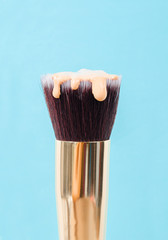 pouring liquid beige makeup foundation on a brush.