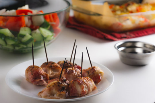 Plate of bacon wrapped scallops on white background.