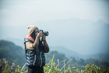 Female tourists take pictures with digital cameras on the mountain.