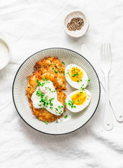 Potato latkes and boiled egg - healthy breakfast or snack on light background, top view