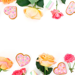 Frame made of roses flowers with cookies and marshmallow on white background. Flat lay