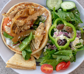 Chicken pita giro and Greek salad.   Healthy eating concept images.
