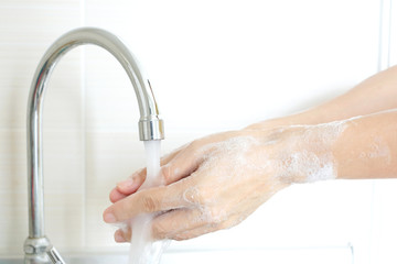 hand of beauty woman  wash your hands at the wash basin with foam, cleanse the skin and have water flowing through the hands. Health and beauty concepts