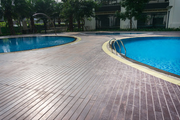 Blue swimming pool with wood flooring stripes