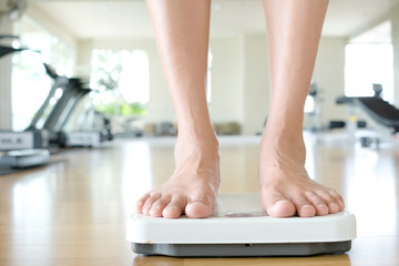 Legs of women standing on scales weight background fitness room. Concept of healthy lifestyle and sport
