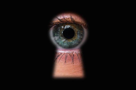 Human eye behind door looking through a keyhole