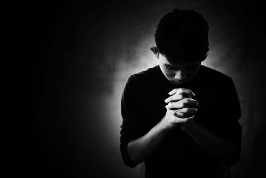 Depress and Hopeless boy praying in the dark in white tone