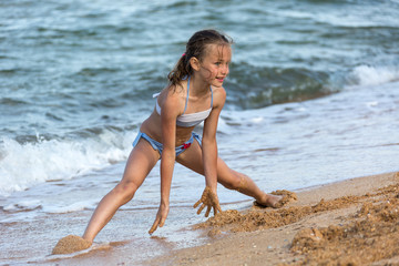 young girl athlete in a swimsuit at sea playing on the beach on the sand, legs open