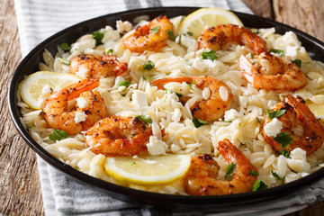 Spicy orzo pasta with grilled shrimps, feta cheese, herbs and lemon close-up on a plate. horizontal