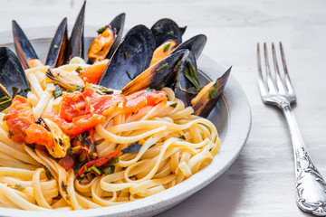 Traditional Italian pasta linguine with mussels on a plate close-up.