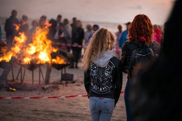 Large burning bonfire with soft glowing flame and sparkles flying all around. Sisters standing together. Romantic summer evening, people relaxing and enjoying calmness at the seaside
