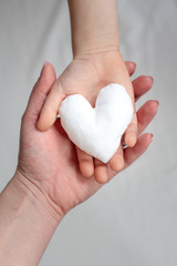 image of two hands holding white fabric heart. Mother and child together
