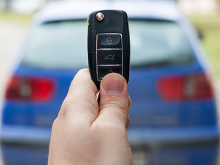 A person holding car key (remote control) in hands on blur blue car background.