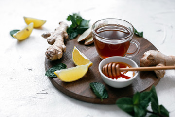Hot tea with ginger, lemon, honey and mint leaves on white table.Tea against cold.Healthcare concept.Useful tea for immunity.Eyer bird view