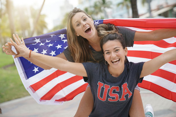 Two dynamic young friends proudly flying the American flag together outdoors