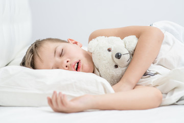 Little boy with toy bear is sleeping with his mouth open, snoring
