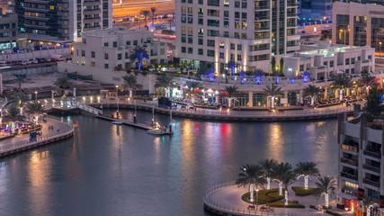 Luxury Dubai Marina canal with passing boats and promenade day to night timelapse, Dubai, United Arab Emirates