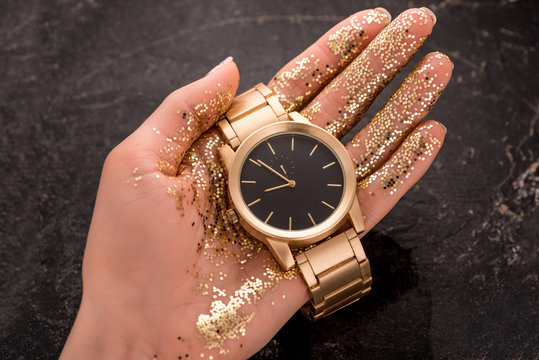 cropped view of golden wristwatch in hand of woman