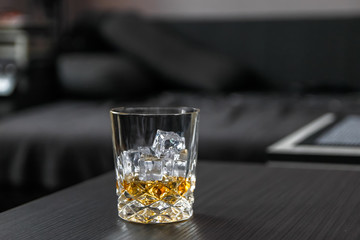 Glass of whiskey with ice cubes on black table