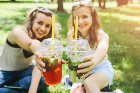 Two hipster girls are laughing and drinking summer cocktails outdoors in the green grass. Cold non-alcoholic drinks with ice to go. Mojito and strawberry lemonade. Happy lifestyle for vacations.