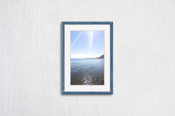 Frame mock up with sea view picture, light blue realistic wooden framework on white plastered wall
