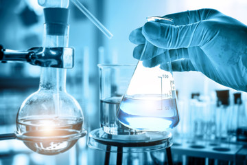 hand of scientist holding flask with lab glassware in chemical laboratory background, science laboratory research and development concept