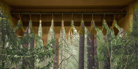 Clothes hanger with dresses in the forest. Concept for organic clothes, closet and sustainable...
