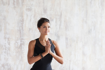 Beautiful young woman yoga instructor in a black gymnastic costume meditates with folded hands in front of the chest. Self care and beauty concept