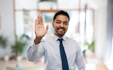 business, gesture and people concept - smiling indian businessman making high five over office background
