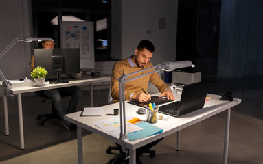 business, technology, design and people concept - young creative man or graphic designer with laptop computer working by pen tablet late at night office