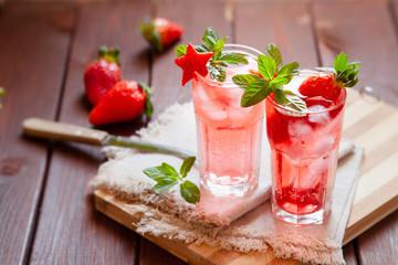 Sparkling pink strawberry lemonade on dark wooden background
