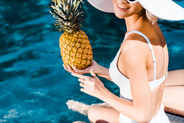 cropped view of woman in swimwear posing with pineapple near swimming pool