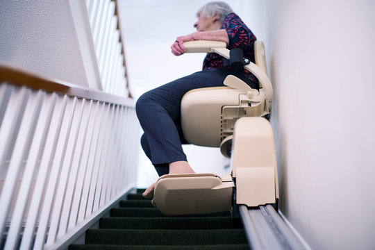Senior Woman Sitting On Stair Lift At Home To Help Mobility