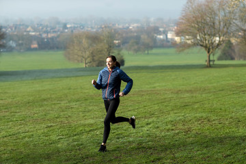 Woman On Early Morning Winter Run Through Park Keeping Fit Through Exercise