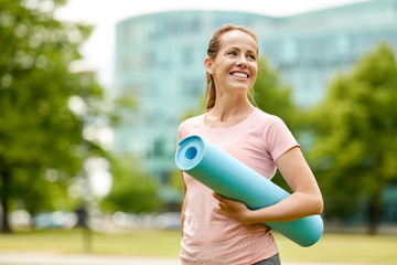 fitness, sport and healthy lifestyle concept - happy smiling woman with exercise mat at city park