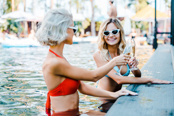 happy blonde girls in sunglasses relaxing in swimming pool with champagne glasses