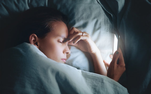 Woman in bed at night with smartphone