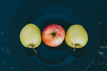 green and red apples on black plate on dark background