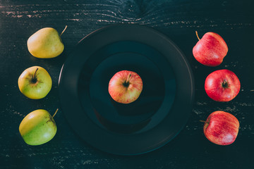 one apple on black plate on dark background and others both green and red outside the dish