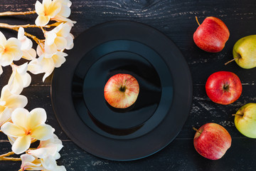 one apple on black plate on dark background and others outside the dish with flowers