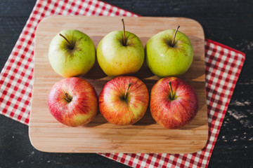 group of apples on wooden cutting board with napkin, close-up shot of organic products and healthy fruit