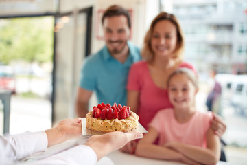 Strawberries cake for girl with parents in confectionery