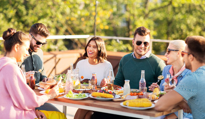 leisure and people concept - happy friends eating and drinking at rooftop party in summer